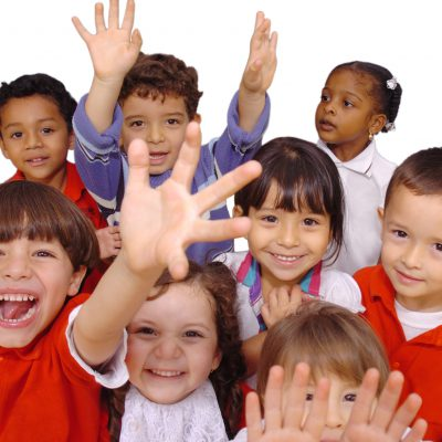 young students smiling and raising their hands towards the camera